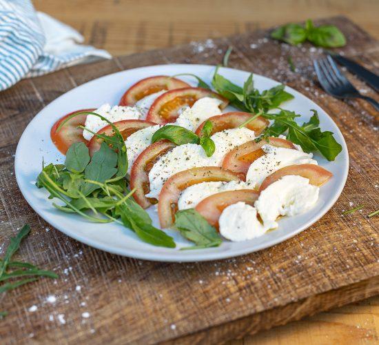 Burrata sobre lecho de ensalada y tomate